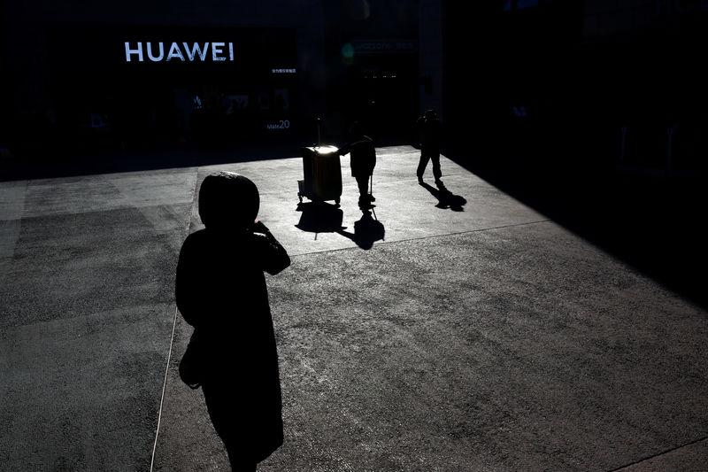 FILE PHOTO: People walk past a Huawei shop in Beijing, China, December 11, 2018. REUTERS/Thomas Peter/File Photo