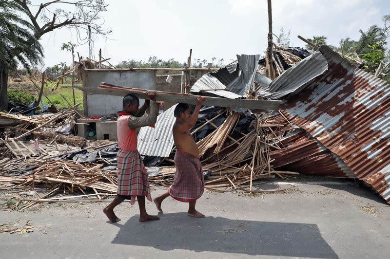 Residents carry tin sheets salvaged from the rubble of a damaged house in the aftermath of Cyclone Amphan, in South 24 Parganas district