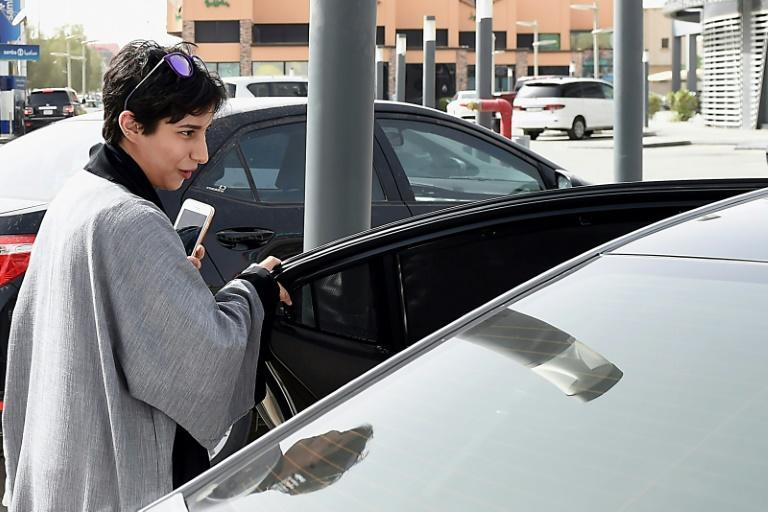 A customer gets into the car of Reem Farahat, a member of popular ride-hailing app Careem's new all-women chauffeur crew in Saudi Arabia, in the capital Riyadh on June 24, 2018