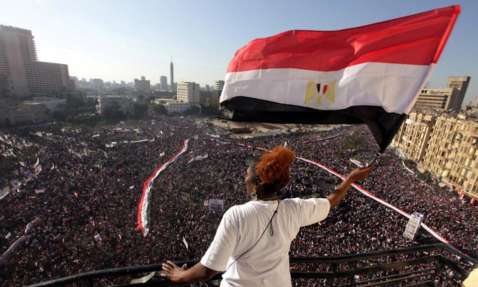 A woman waves the Egyptian flag from a balcony as tens of thousands gather in Tahrir Square in Cairo a week after Hosni Mubarak resigned.