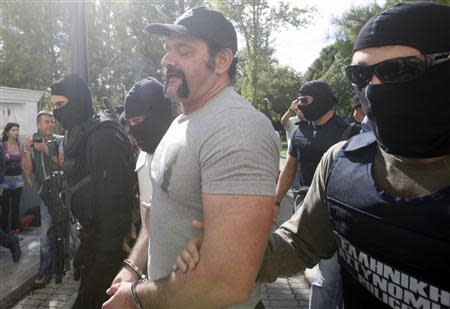 Extreme-right Golden Dawn party lawmaker Lagos is escorted by anti-terrorism police officers in a court in Athens