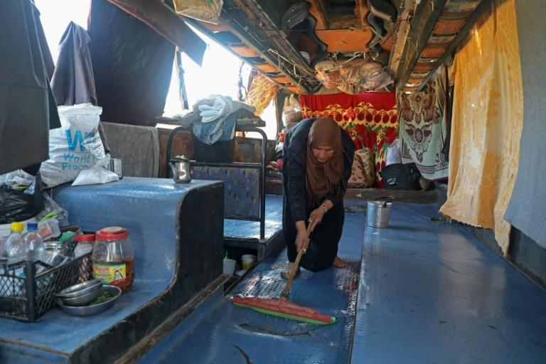 The set-up in the gutted bus where Umm Joumaa lives with her children is rudimentary (AFP Photo/Zein Al RIFAI)