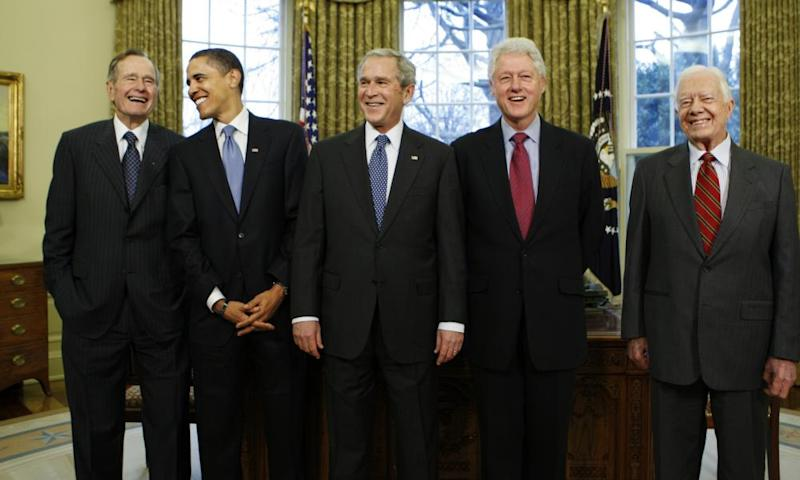 In a picture from January 2009, President-elect Barack Obama is welcomed by President George W Bush, for a meeting at the White House, with George HW Bush, Bill Clinton and Jimmy Carter.