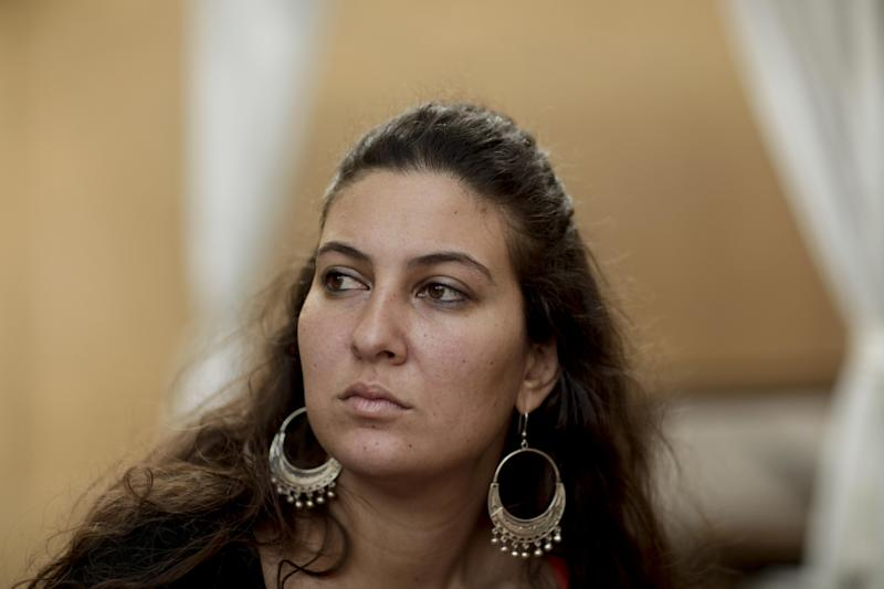 In this Nov. 23, 2012 photo, activist Nazly Hussein pauses during an interview with the Associated Press in Cairo, Egypt. After being detained at a Cairo protest, Hussein was among 14 women, some of Egypt's most prominent democracy advocates, who were beaten, pulled by the hair and piled into a police van, taken on a sinister nighttime ride through the desert where they were finally dumped by the road, the women recount. The abuse, reminiscent of the Hosni Mubarak era, points to how Egypt's new military-backed authorities are becoming bolder in silencing dissent, exploiting the fight against Islamists and divisions among secular activists. (AP Photo/Maya Alleruzzo)