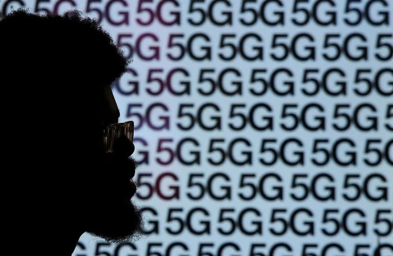 A man walks past an advertisement promoting the 5G data network at a mobile phone store in London