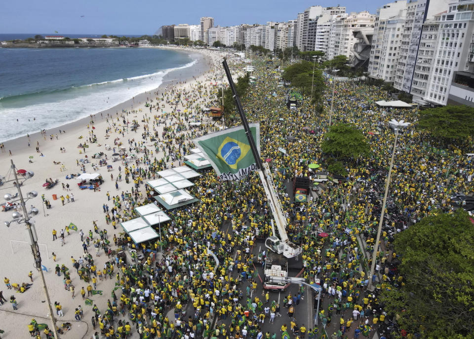 FILE - In this Sept. 7, 2021 file photo, supporters of Brazilian President Jair Bolsonaro gather along Copacabana Beach on Independence Day in Rio de Janeiro, Brazil. People used to watch the sunset from the beach before 2019 when Brazilian President Jair Bolsonaro ended the practice of changing clocks for daylight savings. (AP Photo/Renato Spyroo, File)