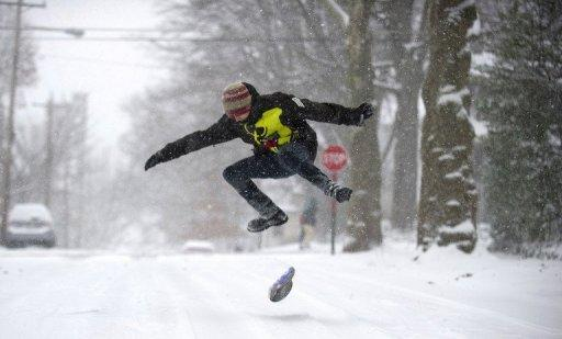 A teenager snowboards down the road December 26, 2012 in Pittsburgh, Pennsylvania
