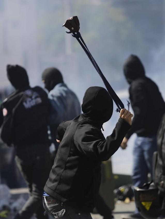 A protester winds up to sling a stone at police after clashes erupted in Sao Paulo, Brazil, Thursday, June 12, 2014. Police clashed with anti-World-Cup protesters who were trying to block a road part of the main highway leading to the stadium that hosts the opening match to the tournament. in Sao Paulo, Brazil, Thursday, June 12, 2014. (AP Photo/Nelson Antoine)