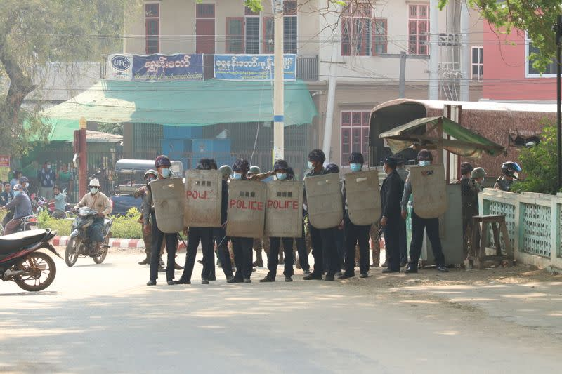 Security force officers hold shields in Nyaung-U