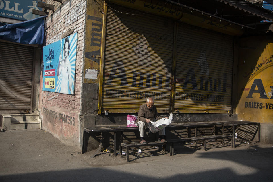 An elderly Kashmiri man reads a newspaper at a closed market during a strike called by separatists in Srinagar, Indian controlled Kashmir, Saturday, Oct. 31, 2020. Kashmir's main separatist grouping called the strike to protest new land laws that India enacted on Tuesday, allowing any of its nationals to buy land in the region. Pro-India politicians in Kashmir have also criticized the laws and accused India of putting Kashmir's land up for sale. The move exacerbates concerns of Kashmiris and rights groups who see such measures as a settler-colonial project to change the Muslim-majority region's demography. (AP Photo/Mukhtar Khan)