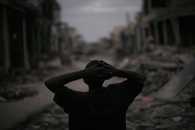 <p>A man pauses in a downtown street in earthquake-torn Port-au-Prince, Monday, Jan. 25, 2010. (Photo: Rodrigo Abd/AP) </p>