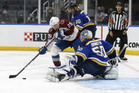 St. Louis Blues goaltender Jordan Binnington (50) defends against Colorado Avalanche's Nathan MacKinnon (29) during the third period in Game 3 of an NHL hockey Stanley Cup first-round playoff series Friday, May 21, 2021, in St. Louis. (AP Photo/Scott Kane)
