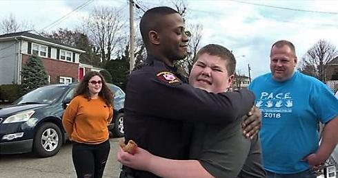 """Officer Khari Manzini poses with Ryan Paul after responding to an emergency call for a """"teddy bear rescue."""" (Credit: Bob Paul)"""