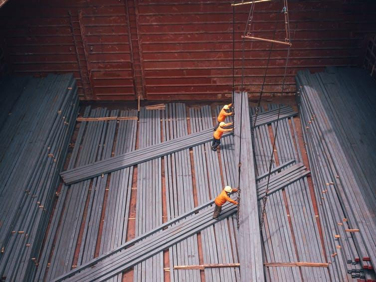 Three workers loading large steel rods
