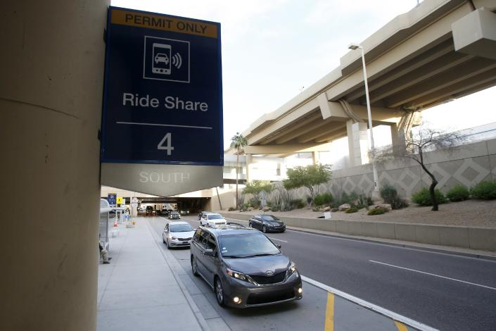 Vehicles wait for their passengers at the Ride Share pickup point at Phoenix Sky Harbor International Airport Wednesday, Dec. 18, 2019, in Phoenix. The Phoenix City Council is set to vote on raising fees charged to ride-hailing companies at the airport. If approved Wednesday afternoon, the proposal will increase the current fee from $2.66 per pickup. That would jump to $4 starting Jan. 1 and be applied to drop-offs as well. (AP Photo/Ross D. Franklin)