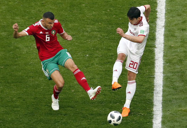 Morocco's Romain Saiss, left, and Iran's Sardar Azmoun, right, challenge for the ball during the group B match between Morocco and Iran at the 2018 soccer World Cup in the St. Petersburg Stadium in St. Petersburg, Russia, Friday, June 15, 2018. (AP Photo/Darko Vojionovic)