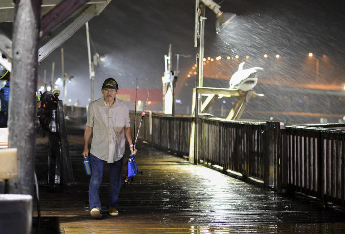 <p>Rogelio Ortiz makes his way off the Pirate's Landing Fishing Pier as rain from Hurricane Harvey falls on Thursday, Aug. 24, 2017, in Port Isabel, Texas. (Photo: Jason Hoekema/The Brownsville Herald via AP) </p>