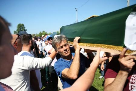 People carry a coffin during a mass funeral in the village of Hambarine