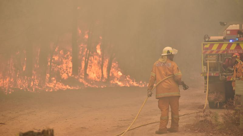 Firefighters create a back burn ahead of a fire front in the New South Wales town of Jerrawangala on January 1, 2020. - A major operation to reach thousands of people stranded in fire-ravaged seaside towns was under way in Australia on January 1 after deadly bushfires ripped through popular tourist spots and rural areas leaving at least eight people dead. (Photo by PETER PARKS / AFP) (Photo by PETER PARKS/AFP via Getty Images)