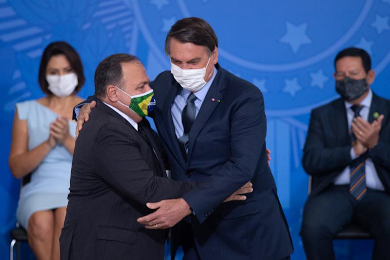 BRASILIA, BRAZIL - SEPTEMBER 16: President of Brazil Jair Bolsonaro and newly appointed Health MinisterEduardo Pazuello hug during his sworn in ceremonyamidst the coronavirus(COVID-19) pandemic at the on September 16, 2020 in Brasilia.Pazuellotook over as interim minister on May 16 this year.Brazil has over 4.382,000 confirmed positive cases of Coronavirus and has over 133,119 deaths.(Photo by Andressa Anholete/Getty Images)