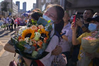 A student wearing a face mask to help curb the spread of the coronavirus with a bouquet of flowers is hugged by her relative at the end of China's national college entrance examinations, known as the gaokao in Beijing, Thursday, June 10, 2021. Millions of students took part in the tough annual exams from which the results determine entrance to the country's top universities. (AP Photo/Andy Wong)