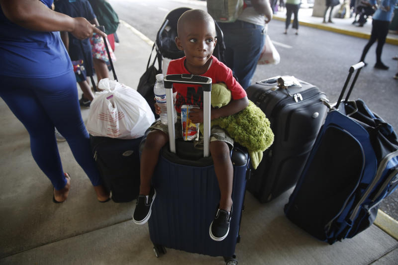"3-year-old Hurricane Dorian evacuee Trevanti Saunders of Freeport, sits on a suitcase with his family as they wait for a ride after arriving on the Grand Celebration cruise ship from Freeport, a city in the Grand Bahamas on Wednesday, Sept. 18, 2019 in Riviera Beach. The cruise ship transported hundreds of evacuees seeking passage from Freeport after the damaged caused by Hurricane Dorian. Saunders mother, Denise Saunders, said ""It was terrifying. We had to run out of the house. The water was reaching us to our chest, water came in very fast. I was crying."" (AP Photo/Brynn Anderson)"