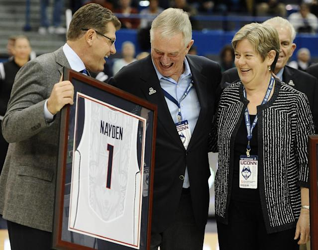 Connecticut head coach Geno Auriemma, left, presents Denis and Britta Nayden with a team jersey before an NCAA college basketball game against UC Davis, Thursday, Dec. 5, 2013, in Hartford, Conn. The Naydens, UConn alumni, have donated $3 million toward the new UConn Basketball Champions Center and for scholarships for student athletes. (AP Photo/Jessica Hill)