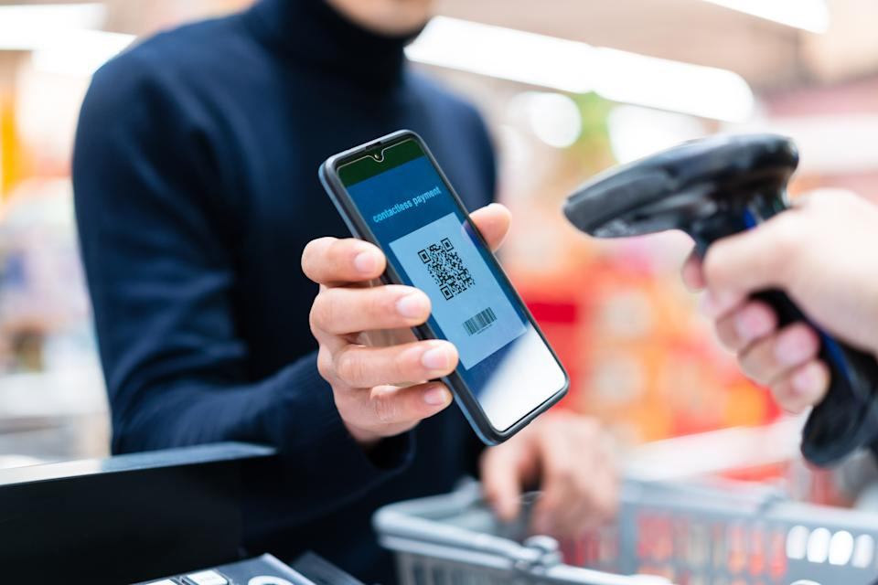 asian man contactless payment with qr code in supermarket