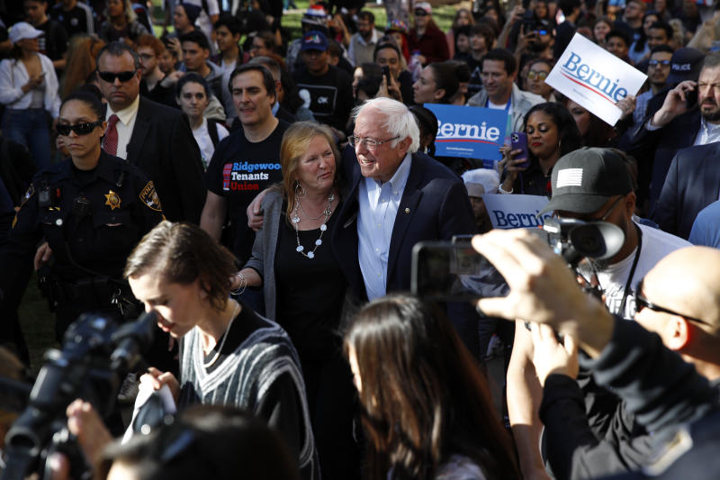 Democratic presidential candidate Sen. Bernie Sanders, I-Vt., and his wife Jane O'Meara Sanders lead supporters to an early voting location after a campaign event at the University of Nevada, Las Vegas, Tuesday, Feb. 18, 2020, in Las Vegas. (AP Photo/Patrick Semansky)