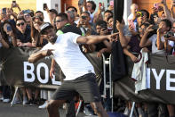 FILE - In this April 2, 2019, file photo, Jamaican sprinter Usain Bolt strikes his now-famous victory pose after defeating a mototaxi in a 50-meter race in Lima, Peru. The retired sprinting great recently had twins, which is keeping him plenty busy. He thinks one of the favorites to win the 100 meters at the Tokyo Games is American Trayvon Bromell. (AP Photo/Martin Mejia, File)