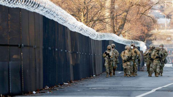 PHOTO: A group of Virginia National Guard patrol around the razor wire fence surrounding the U.S. Capitol grounds in Washington, Jan. 16, 2021.  (Samuel Corum/Getty Images)