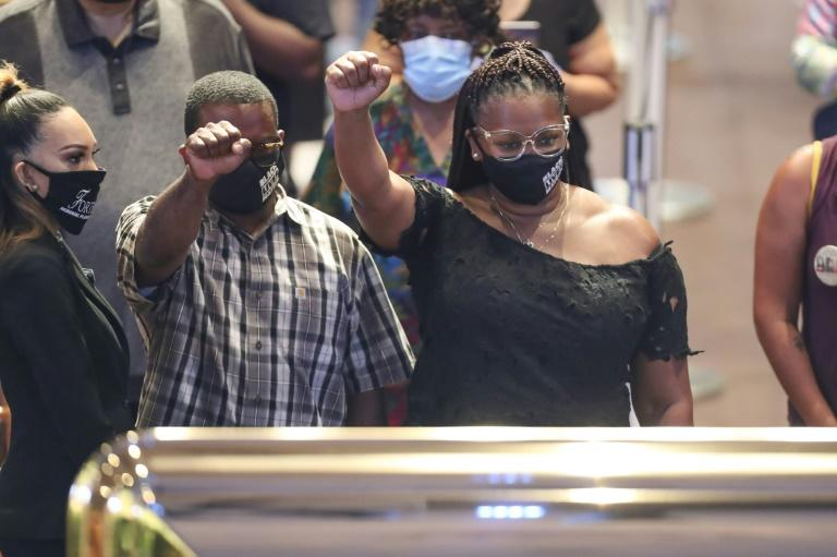 Mourners raise their fists, a symbol of black power and solidarity, over the casket of George Floyd during a public viewing at The Fountain of Praise church in Houston (AFP Photo/Godofredo A. VASQUEZ)