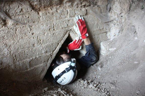 Someone from Underground Rome works their way through a narrow cavity into the underground tunnels of Hadrian's Villa