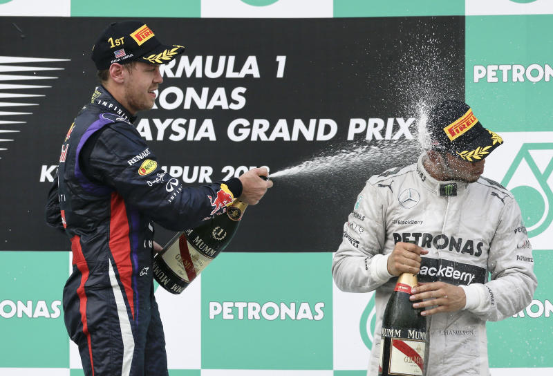 Red Bull driver Sebastian Vettel of Germany, left, sprays champagne to Mercedes' Lewis Hamilton of Britain after the awarding ceremony for the Malaysian Formula One Grand Prix at Sepang, Malaysia, Sunday, March 24, 2013. Vettel won the race and Hamilton finished third. (AP Photo/Andy Wong)