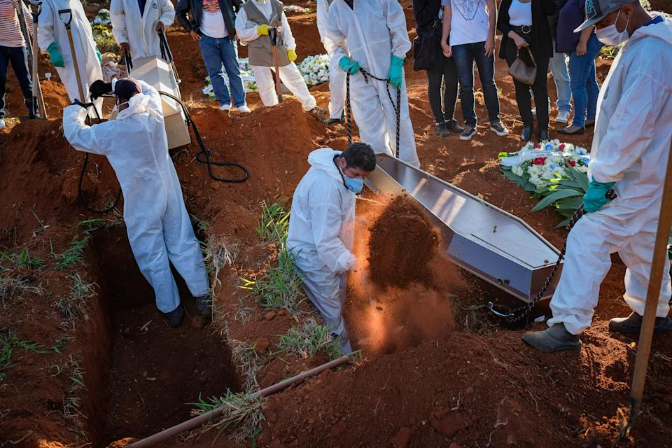 14 October 2020, Brazil, Sao Paulo: Cemetery workers in protective suits shoveling earth during a funeral at the Vila Formosa cemetery in the middle of the Corona pandemic. The Ministry of Health has confirmed 955 377 Covid-19 infected and 46 510 coronavirus deaths. More than a quarter of the newly registered deaths occurred in the state of São Paulo. Photo: Lincon Zarbietti/dpa (Photo by Lincon Zarbietti/picture alliance via Getty Images)