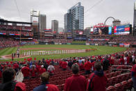 Fans stand along with members of the St. Louis Cardinals and Milwaukee Brewers for the singing of the Star Spangled Banner before the start of a baseball game Thursday, April 8, 2021, in St. Louis. (AP Photo/Jeff Roberson)