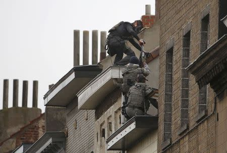 Belgian special forces police climb high on an apartment block during a raid, in search of suspected muslim fundamentalists linked to the deadly attacks in Paris, in the Brussels suburb of Molenbeek, November 16. 2015. REUTERS/Yves Herman
