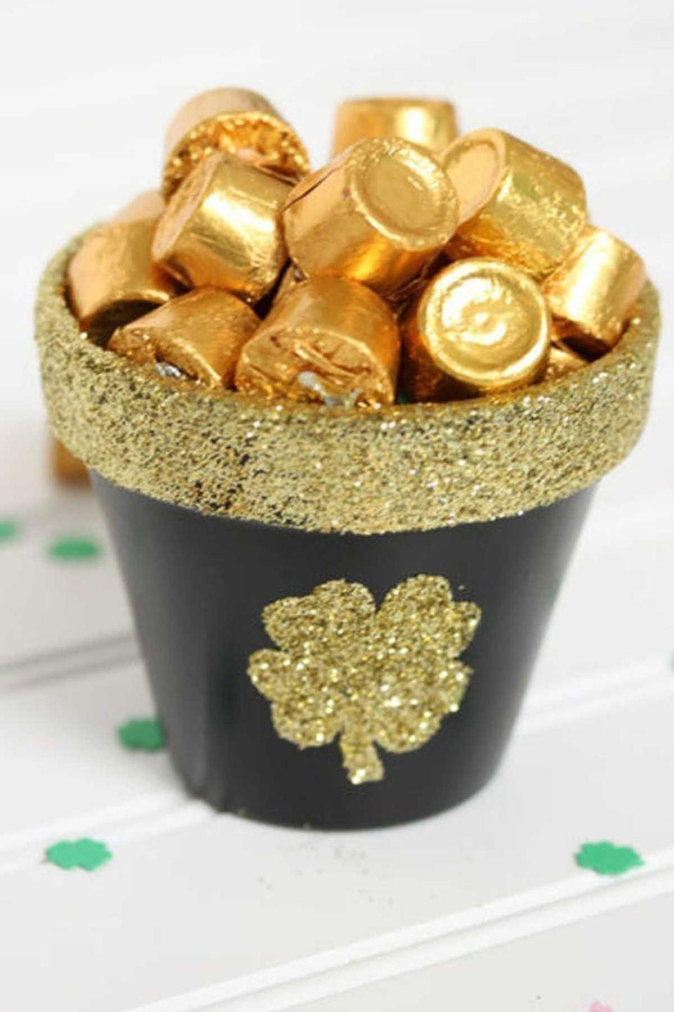 """<p>What's better than a pot of gold you can eat? Filled with candy, here's how to turn an ordinary <a href=""""https://www.womansday.com/home/decorating/a8709/best-flowers-for-spring-house-beautiful/"""" rel=""""nofollow noopener"""" target=""""_blank"""" data-ylk=""""slk:flower pot"""" class=""""link rapid-noclick-resp"""">flower pot</a> into the perfect seasonal craft.</p><p><em>Get the tutorial at <a href=""""http://www.the36thavenue.com/st-patricks-day-pot-of-gold/"""" rel=""""nofollow noopener"""" target=""""_blank"""" data-ylk=""""slk:The 36th Avenue"""" class=""""link rapid-noclick-resp"""">The 36th Avenue</a>.</em> </p>"""