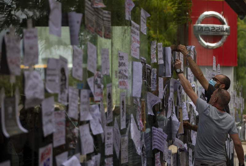 FILE - In this May 29, 2020, file photo, Nissan workers fix leaflets on a car dealerships window during a protest in Barcelona, Spain. Nissan Chief Executive Makoto Uchida told shareholders Monday, June 29, 2020 he is giving up half his pay as the Japanese automaker sank into the red amid plunging sales and plant closures in Spain and Indonesia. (AP Photo/Emilio Morenatti, File)