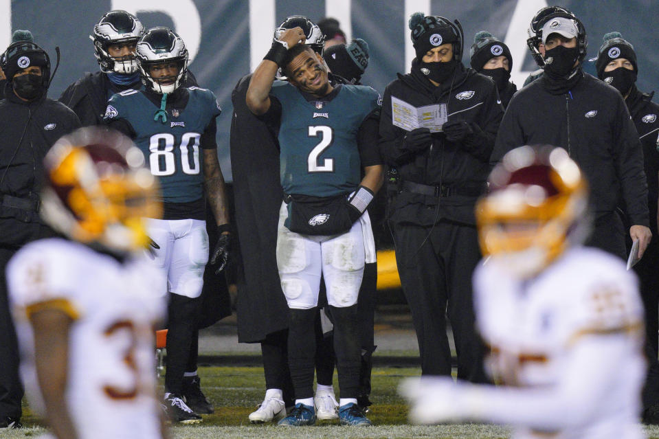 Philadelphia Eagles' Jalen Hurts scratches his head on the sideline during the second half of an NFL football game against the Washington Football Team, Sunday, Jan. 3, 2021, in Philadelphia. (AP Photo/Chris Szagola)
