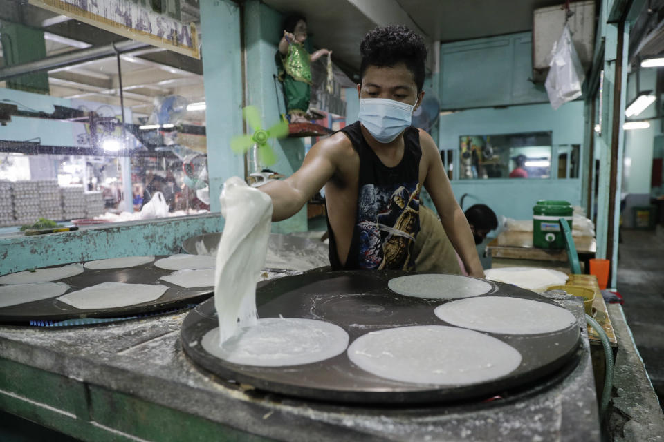 Mark Fulgencio cooks spring roll wrappers at a market in Quezon city, Philippines, Saturday Sept. 26, 2020. Government orders people in public areas to wear face masks to help curb the spread of the coronavirus. (AP Photo/Aaron Favila)