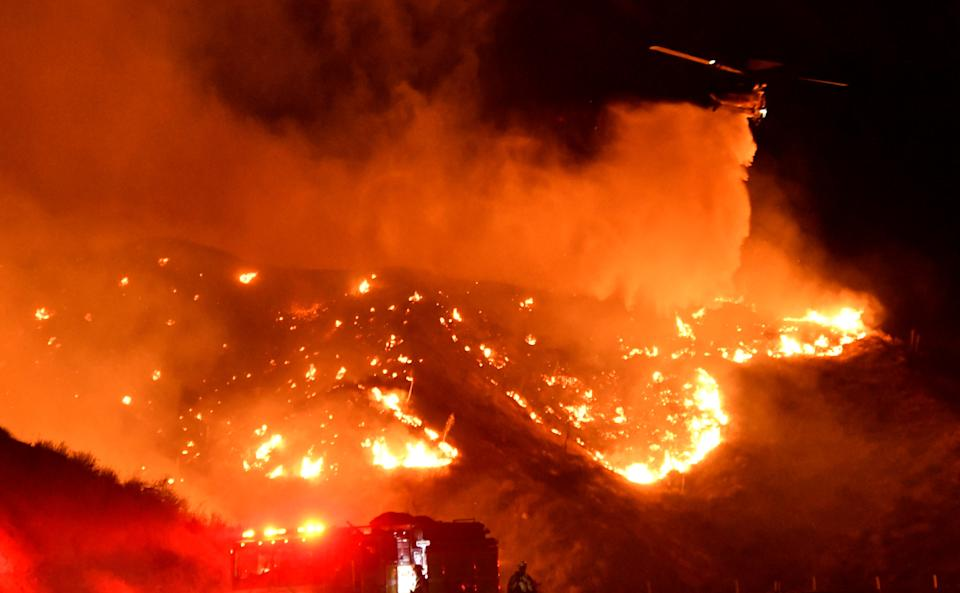 A helicopter makes a water drop, as a wind driven wildfire continues to burn in Canyon Country north of Los Angeles, California, Oct. 25, 2019. (Photo: Gene Blevins/Reuters)