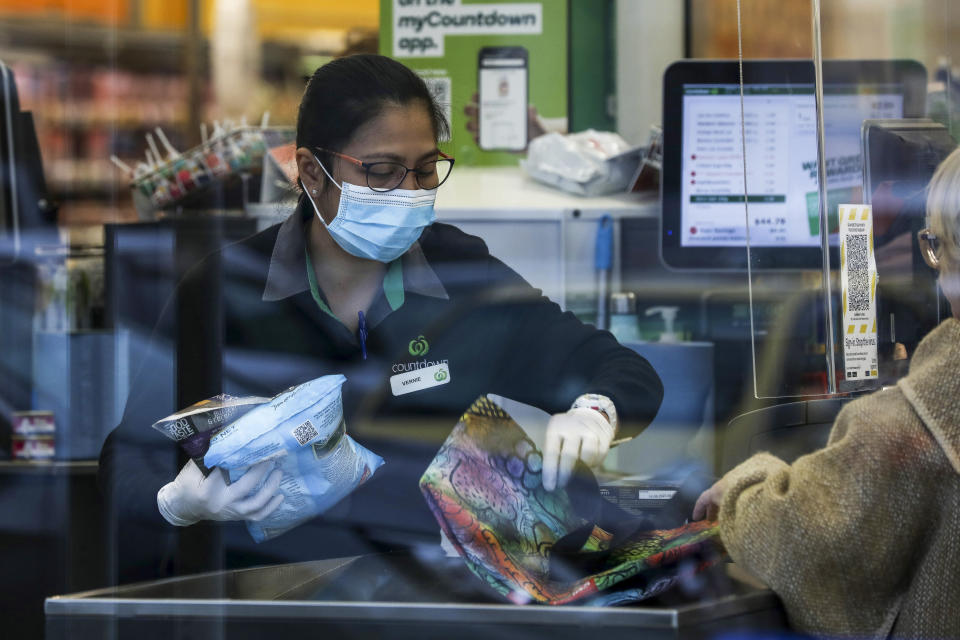 Supermarket staff help a customer with her shopping in Auckland, New Zealand, Tuesday, Aug. 17, 2021. New Zealand's government took drastic action Tuesday by putting the entire nation into a strict lockdown after detecting just a single community case of the coronavirus. (Hayden Woodward/New Zealand Herald via AP)