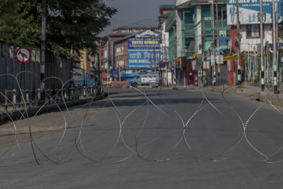 A barbwire blocks a deserted street on the first anniversary of India's decision to revoke the disputed region's semi-autonomy, in Srinagar, Indian controlled Kashmir, Wednesday, Aug. 5, 2020. Last year on Aug. 5, India's Hindu-nationalist-led government of Prime Minister Narendra Modi stripped Jammu-Kashmir of its statehood and divided it into two federally governed territories. Late Tuesday, authorities lifted a curfew in Srinagar but said restrictions on public movement, transport and commercial activities would continue because of the coronavirus pandemic. (AP Photo/ Dar Yasin)