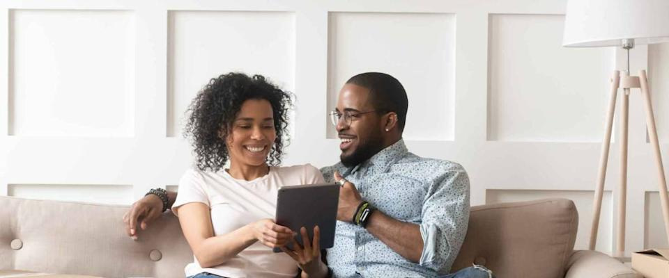 Happy african couple husband and wife shopping online for a mortgage