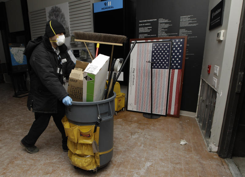 """A 9-11 Memorial worker wheels clean-up equipment through the World Trade Center Memorial visitor center late Monday as work continues to get it up and running after it was damaged by flooding from Superstorm Sandy, Monday, Nov. 5, 2012, in New York.  The World Trade Center Memorial will re-open to the public Tuesday. Parts of the visitor center and a special room for victims' families were damaged by four feet of water, as was some of the museum that is being built. But """"the most sacred"""" point of the memorial remains intact the reflective fountains ringed by the names of the dead. (AP Photo/Kathy Willens)"""