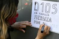 A supporter of Argentine football legend Diego Maradona writes a message outside the Ipensa clinic in La Plata where the star was admitted for medical checks on Monday