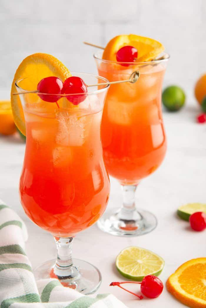 """<p>Hear us out: Yes, the official cocktail of NOLA is the <a href=""""https://www.npr.org/templates/story/story.php?storyId=91912549#:~:text=The%20Louisiana%20House%20of%20Representatives,%E2%80%94%20New%20Orleans'%20official%20cocktail."""" rel=""""nofollow noopener"""" target=""""_blank"""" data-ylk=""""slk:Sazerac"""" class=""""link rapid-noclick-resp"""">Sazerac</a>, but if there was an official drink of Mardi Gras, it'd be the Hurricane. And that's exactly why no Mardi Gras party (yes, eating beignets on your couch counts, too!) is complete without the bright and boozy cocktail, which includes two types of rum, passion fruit juice, orange juice, freshly-squeezed lime juice, simple syrup, and grenadine. (Bonus points if you serve it in the tall glass—that resembles a hurricane lamp—that it was <a href=""""https://www.neworleans.com/drink/cocktails/hurricane/"""" rel=""""nofollow noopener"""" target=""""_blank"""" data-ylk=""""slk:named after"""" class=""""link rapid-noclick-resp"""">named after</a>.)</p><p><a class=""""link rapid-noclick-resp"""" href=""""https://grandbaby-cakes.com/new-orleans-hurricane-drink/"""" rel=""""nofollow noopener"""" target=""""_blank"""" data-ylk=""""slk:GET THE RECIPE"""">GET THE RECIPE </a></p>"""