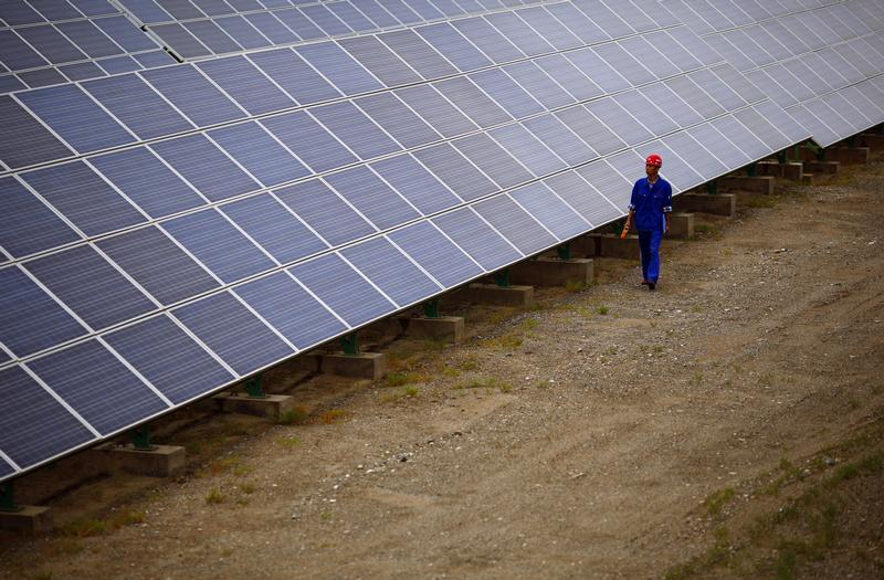 A worker inspects solar panels at a solar farm in Dunhuang, 950km northwest of Lanzhou, Gansu Province