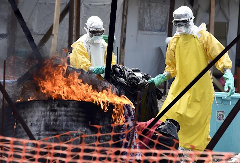 Medical staff members burn clothes belonging to patients suffering from Ebola, at a clinic run by the international medical NGO Doctors Without Borders, September 27, 2014 in Monrovia (AFP Photo/Pascal Guyot)